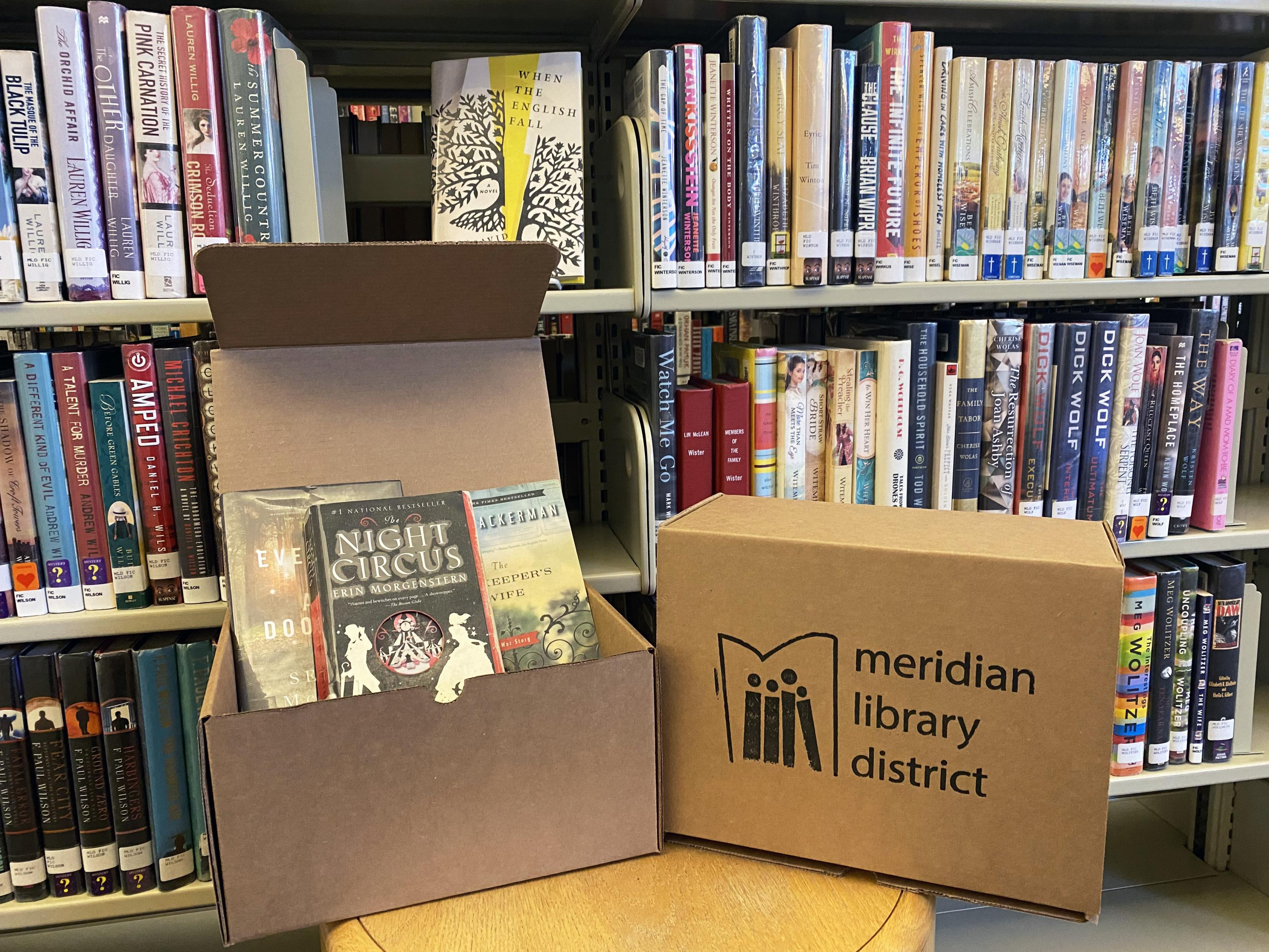 open box with a trio of books and library logo