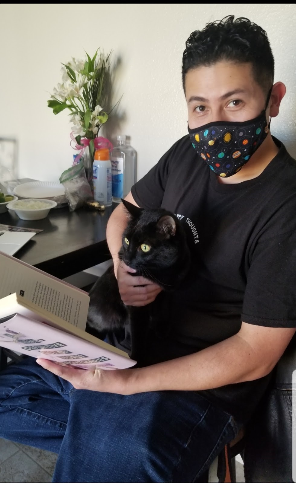 Israel sits at a table with a black cat in his lap, reading a book.