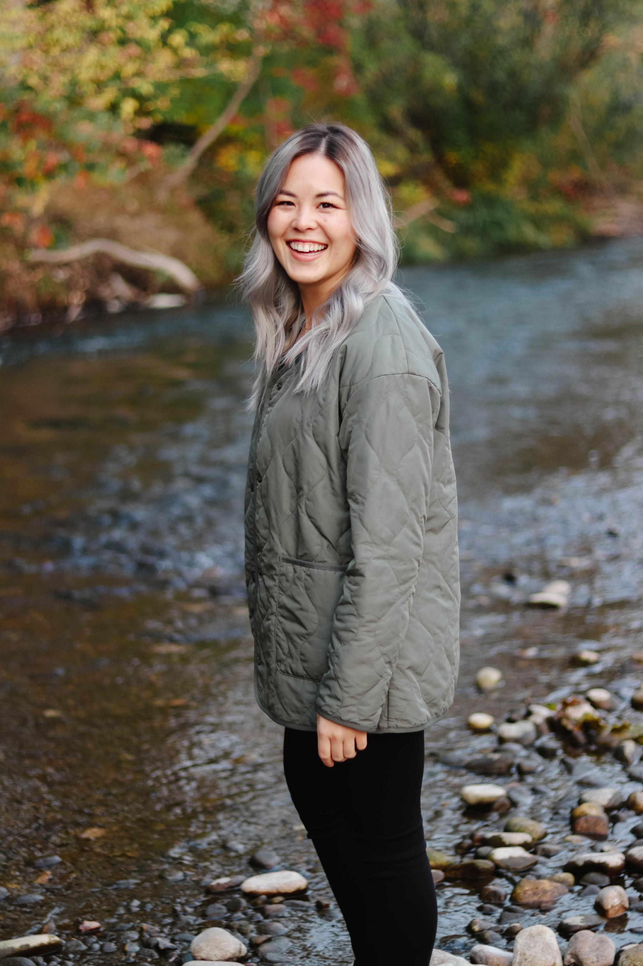 Yuki stands near a river with fall foliage in the background.